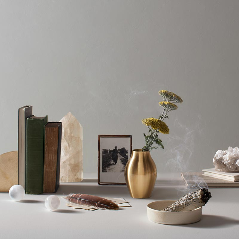 sage burning in dish with feather and books