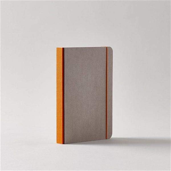 a grey covered journal with rounded corners and a dark orange linen spine with a matching elastic cord