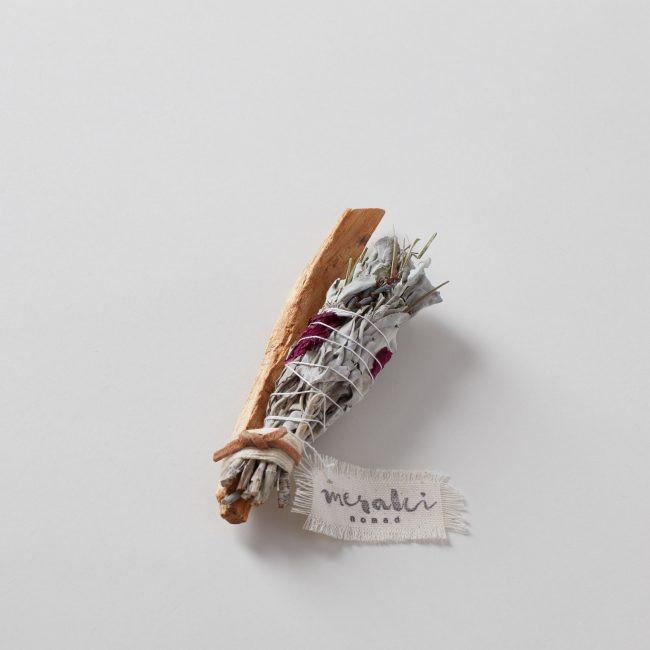 dried white sage bundled with palo santo tied with string