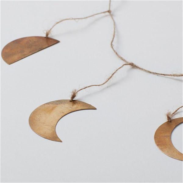close up three phases of the moon in brass strung on jute twine