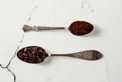 spoonful of whole coffee beans and spoonful of ground coffee