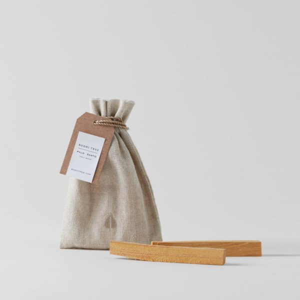 linen pouch tied with string and a label and two palo santo stick in foreground