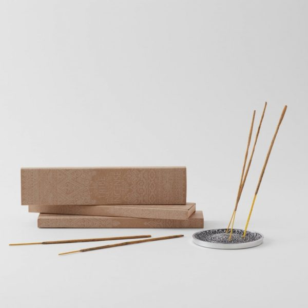 3 boxes of incense with 3 incense sticks set into silver incense holder and two laying out on table