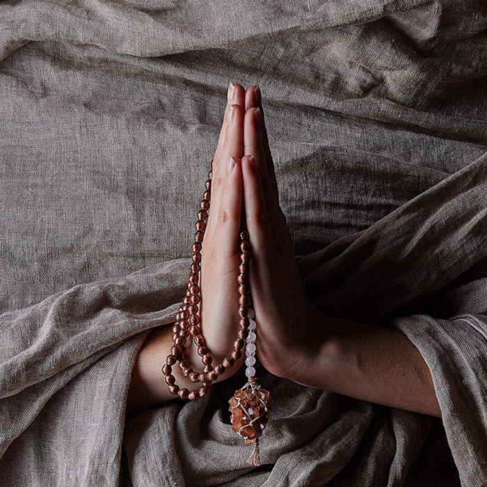 hands in prayer with mala beads