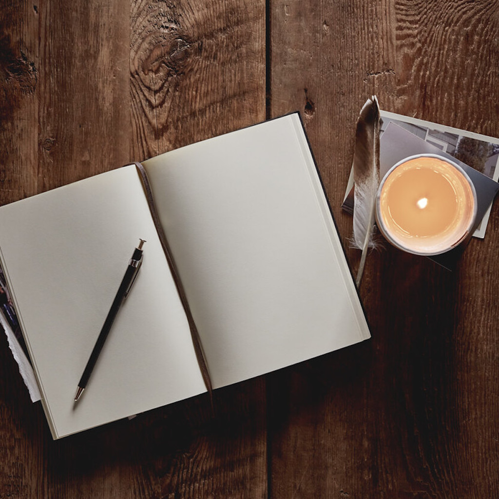 blank journal with pen on desk next to candle and feather