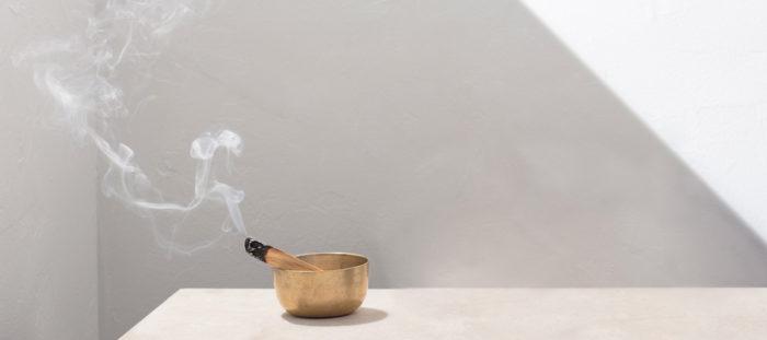 sage smudge stick burning in bowl