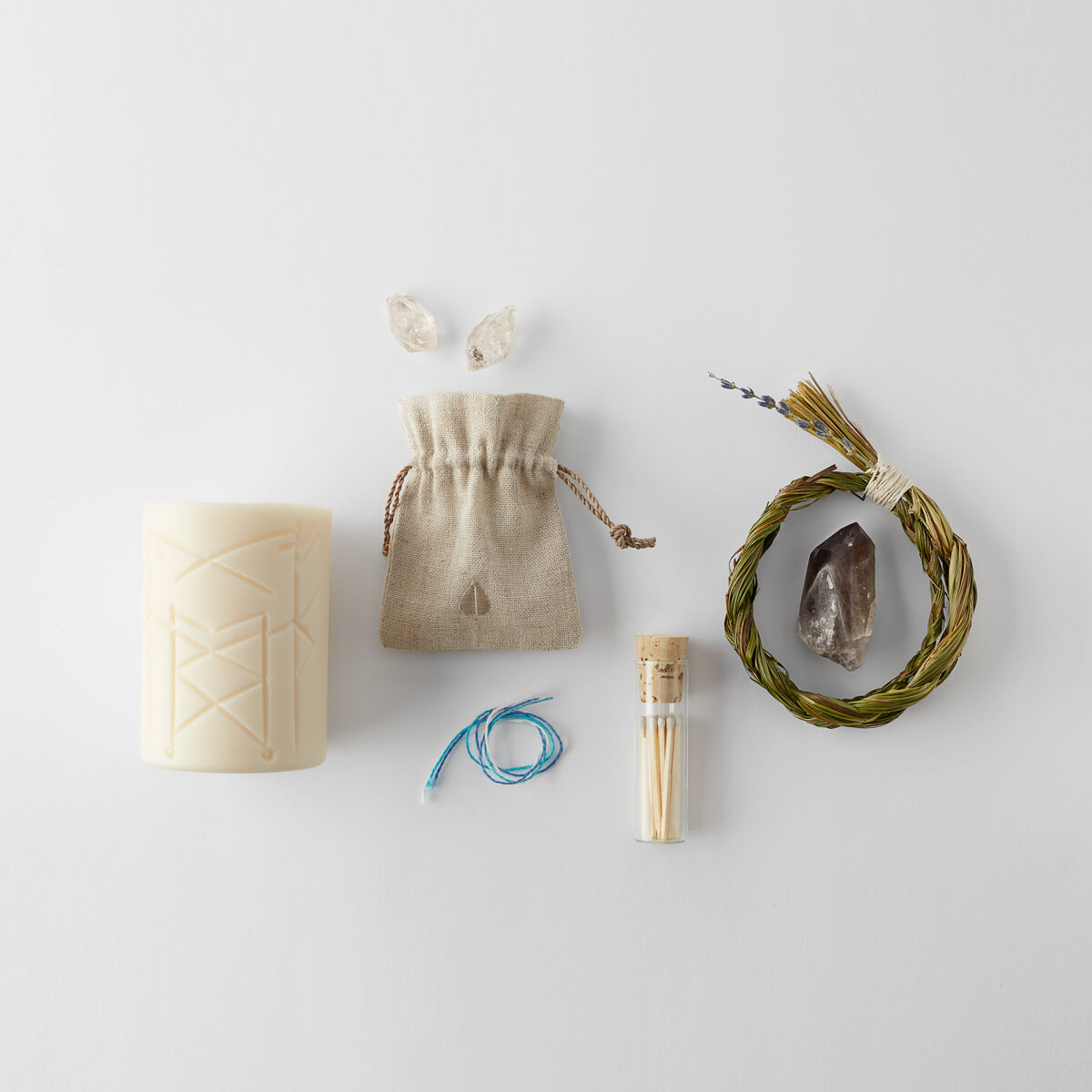 a bundle of sweetgrass, a Smells Like Spells Magic Nordic Rune candle, three strands of ethically sourced recycled linen yarn, a vial of matches, a smoky quartz point crystal and two Herkimer diamonds.