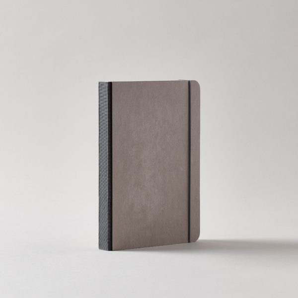 a grey covered journal with rounded corners and a dark dark gray linen spine with a matching elastic cord