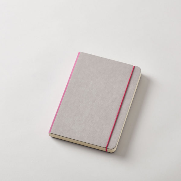 a grey covered journal with rounded corners and a dark pink linen spine with a matching elastic cord