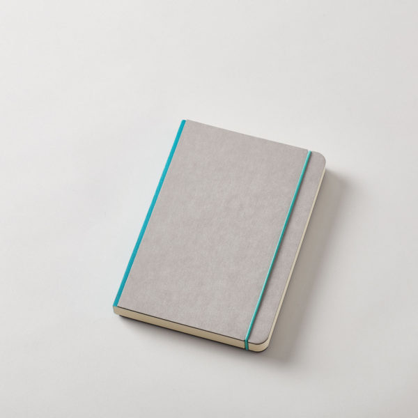 a grey covered journal with rounded corners and a turquoise linen spine with a matching elastic cord
