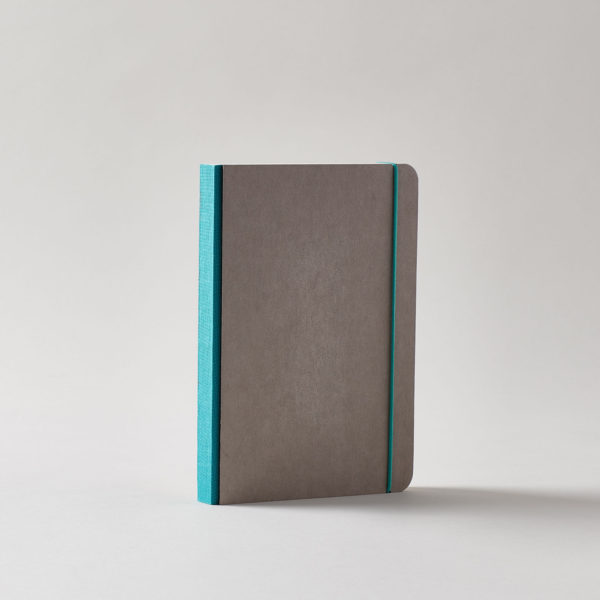a grey covered journal with rounded corners and a dark turquoise linen spine with a matching elastic cord