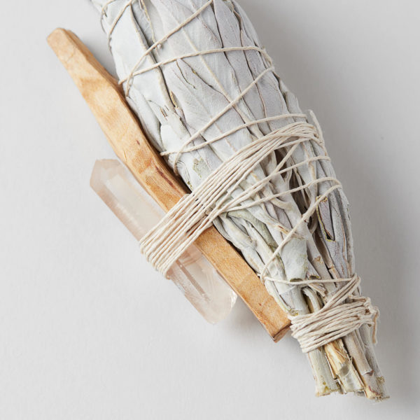 close up of a bundle of California white sage, palo santo and a seed crystal wrapped with string