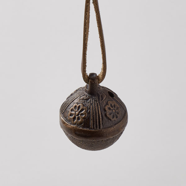 close up of a brass bell with leather hanger