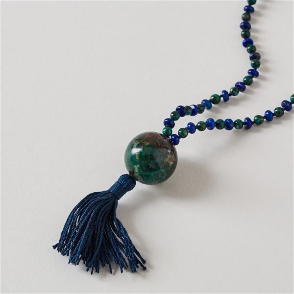 close up of mala with blue green beads and blue tassel