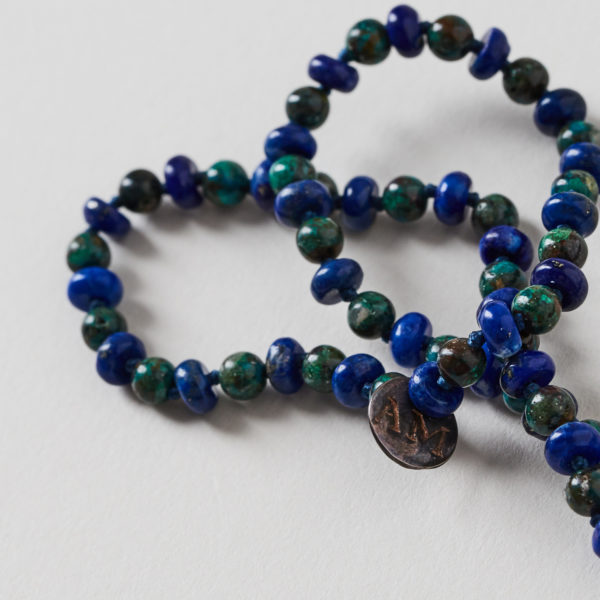 close up of mala with blue and green beads