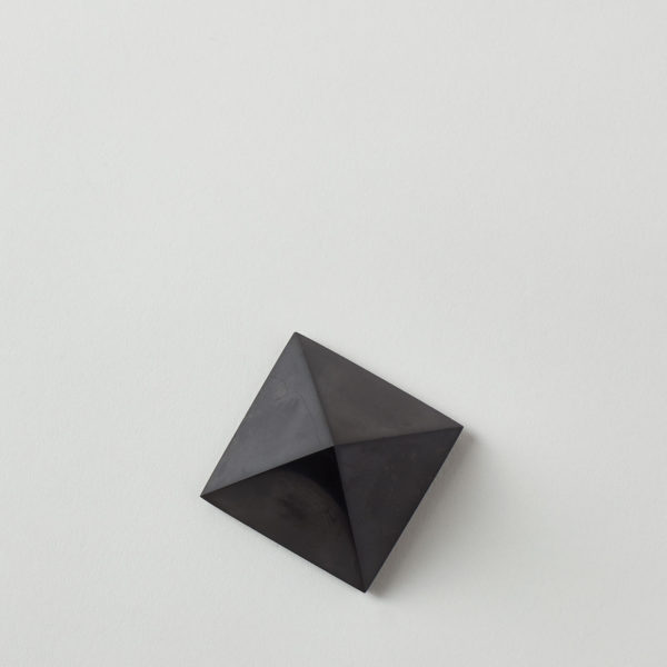 top of a jet black carbon stone, cut and polished into a pyramid shape