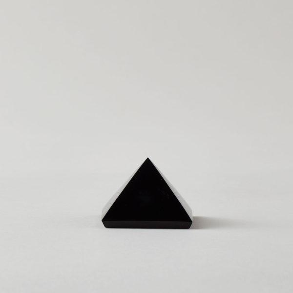 A jet black carbon stone, cut and polished into a pyramid shape