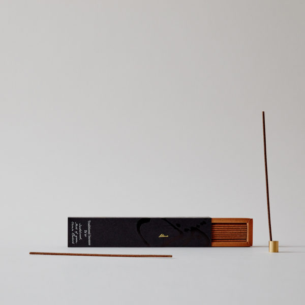 open box of incense with one stick in holder