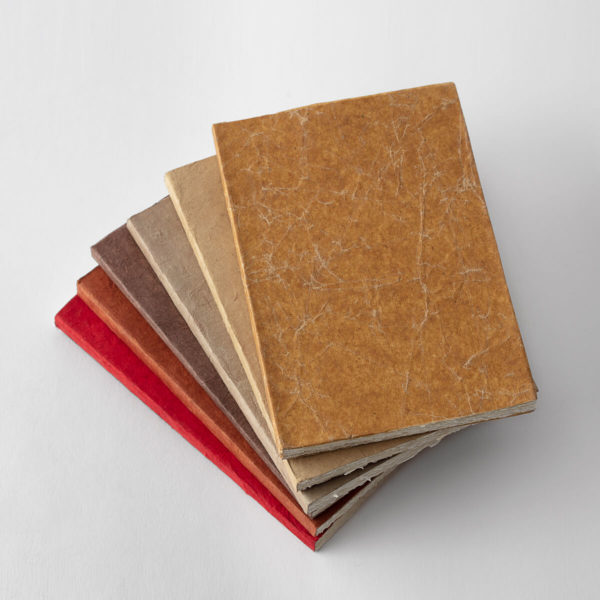 stack of journals in warm autumn colors: orange, rust, kraft, brown