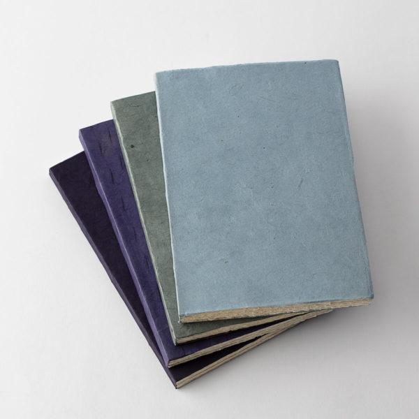 stack of 4 velvet covered journals in black, dark blue, green and light blue
